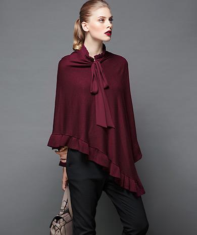 asymmetric knit poncho with boat neckline and ruffles hem.